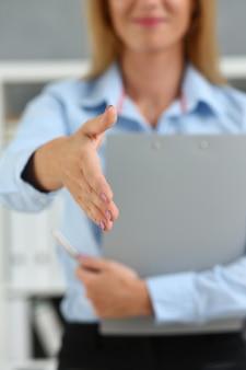 Geschäftsfrau bieten hand, um als hallo im büro zu schütteln