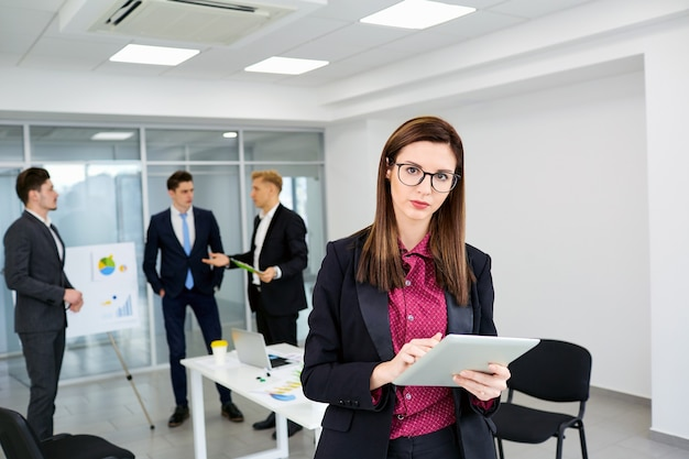 Geschäftsfrau brünette in gläsern auf hintergrundgeschäftsleuten ein büro