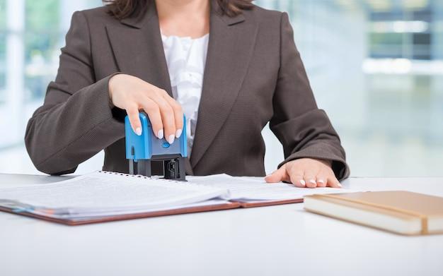 Geschäftsfrau, büroangestellte, die dokumente stempeln, vertrag abschließen, einen deal machen, geschäftskonzept