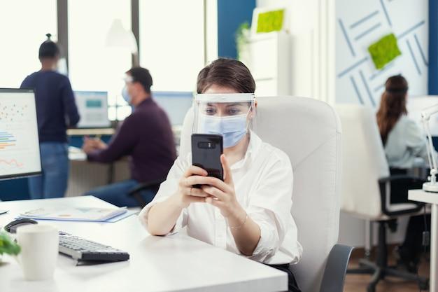 Geschäftsfrau chattet auf dem smartphone, das an ihrem arbeitsplatz in einem geschäftigen büro sitzt und während der globalen pandemie mit covid19 gesichtsmaske trägt. multiethnische mitarbeiter, die in der finanzwelt unter wahrung der sozialen distanz arbeiten