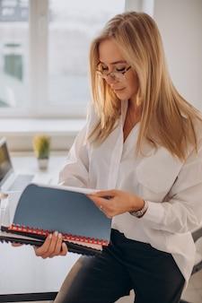 Geschäftsfrau, die akten im büro hält