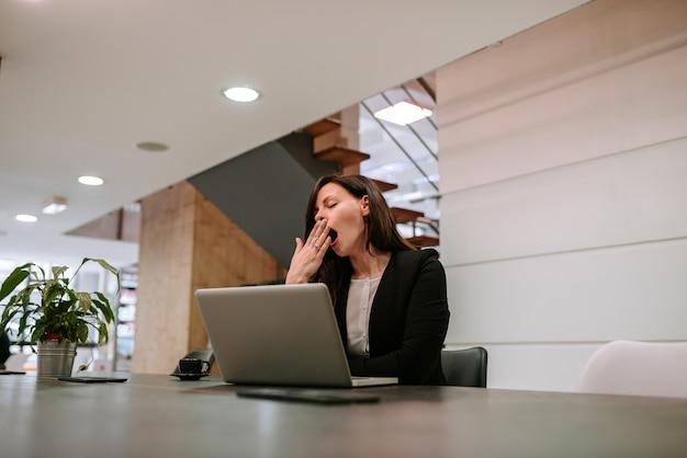 Geschäftsfrau, die am arbeitsplatz gähnt.