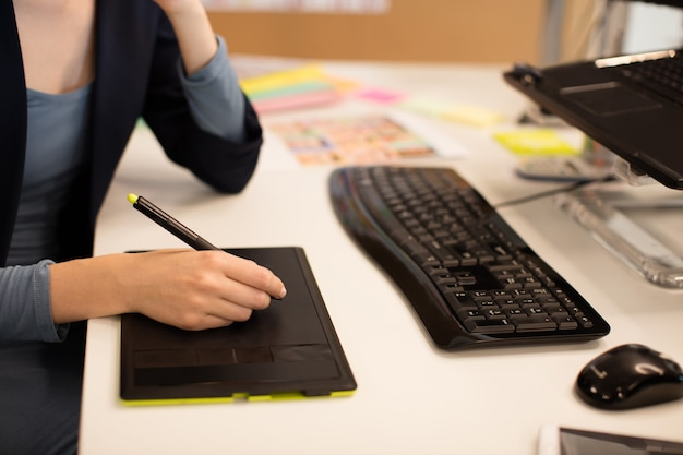 Geschäftsfrau, die am digitalisierer am schreibtisch arbeitet