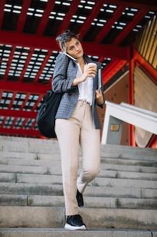 Geschäftsfrau, die am handy hält mitnehmerkaffeetasse und digitaler tablette spricht