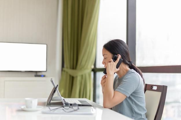 Geschäftsfrau, die am handy spricht, während sie an ihrem tablet im büro arbeitet