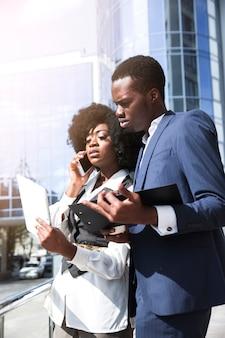 Geschäftsfrau, die am handy steht mit seinem kollegen hält klemmbrett spricht
