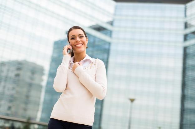 Geschäftsfrau, die am handy vor büro spricht