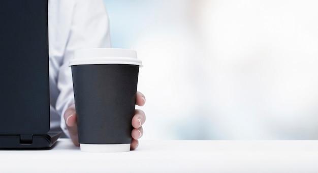 Geschäftsfrau, die am laptop arbeitet und morgenkaffee im büro trinkt