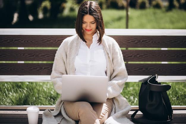 Geschäftsfrau, die am laptop außerhalb des parks arbeitet