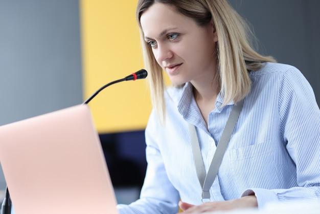 Geschäftsfrau, die am laptop sitzt und mikrofon spricht