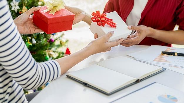 Geschäftsfrau, die am letzten arbeitstag ein geschenk im amt austauscht. junge kreative leute feiern urlaub im modernen büro.