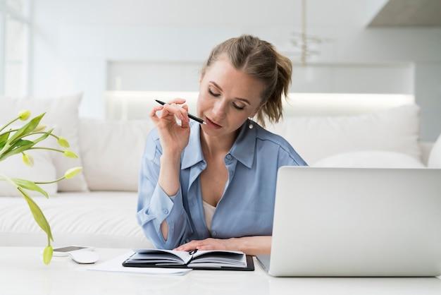 Geschäftsfrau, die am schreibtisch denkt