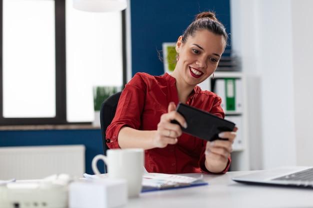 Geschäftsfrau, die am schreibtisch im firmenbüro sitzt und videospiele spielt