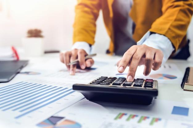 Geschäftsfrau, die am schreibtisch mit taschenrechner und laptop arbeitet, die finanzbuchhaltung analysieren