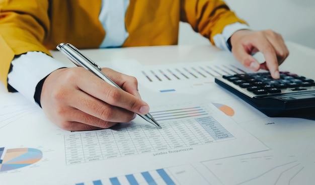 Geschäftsfrau, die am schreibtisch mit taschenrechner und laptop arbeitet, die finanzen analysieren