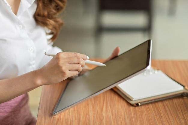 Geschäftsfrau, die am schreibtisch sitzt und einen drahtlosen tablet-pc mit unscharfem leeren bildschirm verwendet