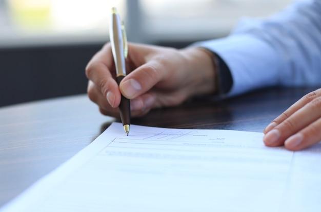 Geschäftsfrau, die am schreibtisch sitzt und einen vertrag mit flachem fokus auf unterschrift unterzeichnet.