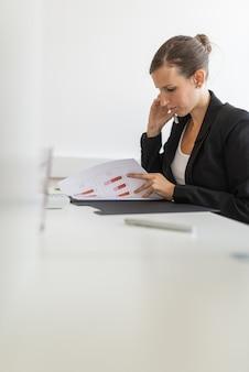 Geschäftsfrau, die am schreibtisch sitzt und geschäftsfinanzbericht mit graphen und diagrammen sucht.