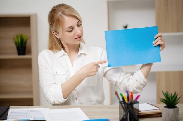 Geschäftsfrau, die am schreibtisch sitzt und leeres papier hält.