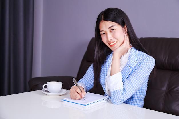 Geschäftsfrau, die am schreibtisch sitzt und schreibt eine anmerkung über das notizbuch