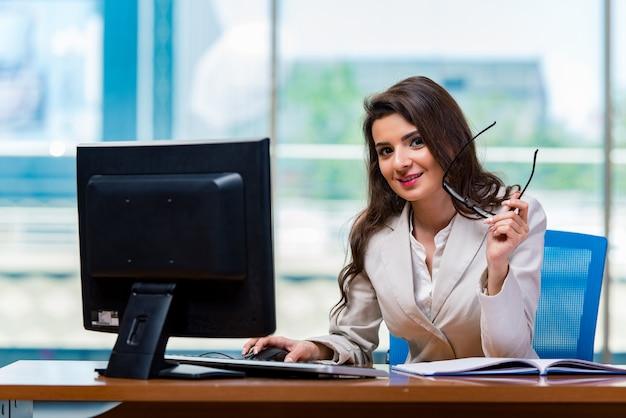 Geschäftsfrau, die am schreibtisch sitzt