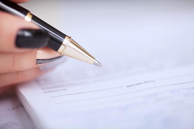 Geschäftsfrau, die am schreibtisch unterzeichnet einen vertrag mit flachem fokus auf unterzeichnung sitzt.