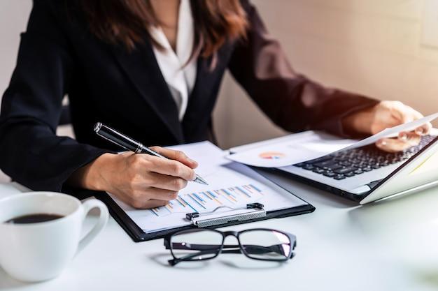 Geschäftsfrau, die am schreibtischbüro mit computer- und marketinggraphstatistikanalyse arbeitet