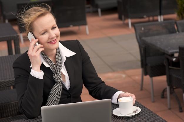 Geschäftsfrau, die am telefon bei draußen sich entspannen mit laptop und tasse kaffee spricht