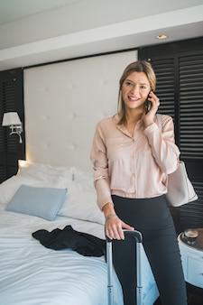 Geschäftsfrau, die am telefon im hotelzimmer spricht