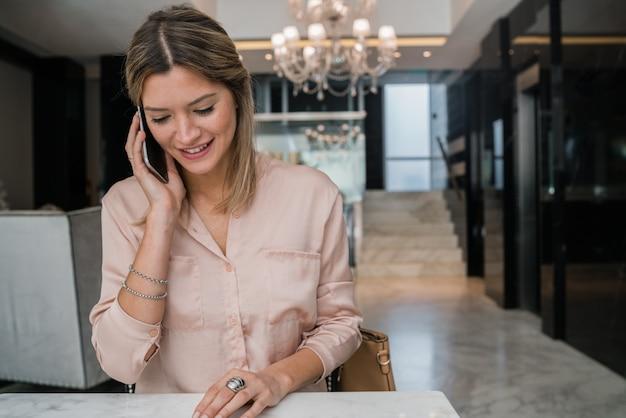 Geschäftsfrau, die am telefon in der hotellobby spricht.