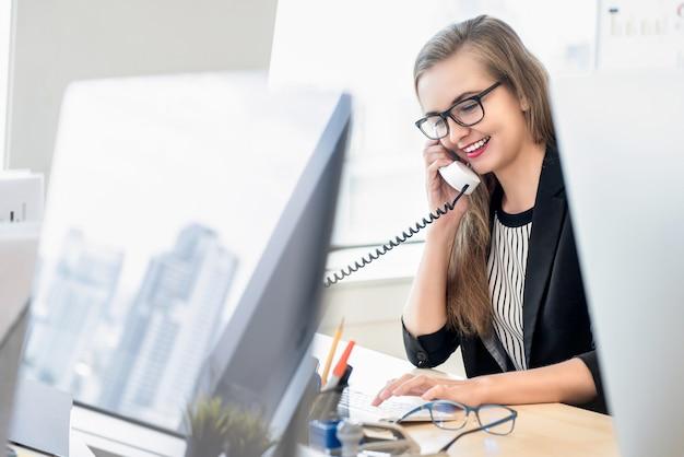 Geschäftsfrau, die am telefon mit kunden bei der arbeit spricht