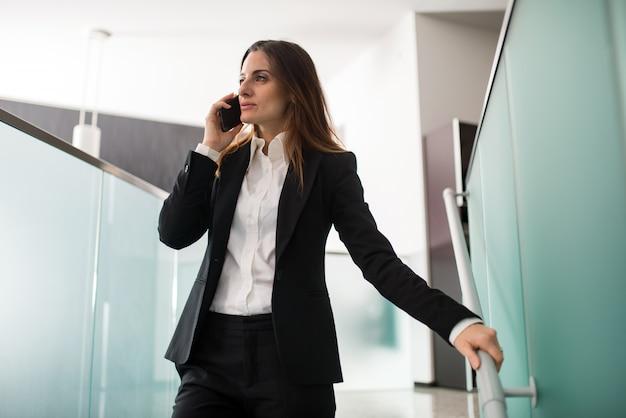 Geschäftsfrau, die am telefon spricht, während sie die treppe in ihrem büro hinuntergeht