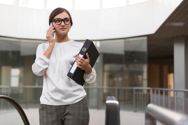 Geschäftsfrau, die am telefon spricht, während sie ordner hält