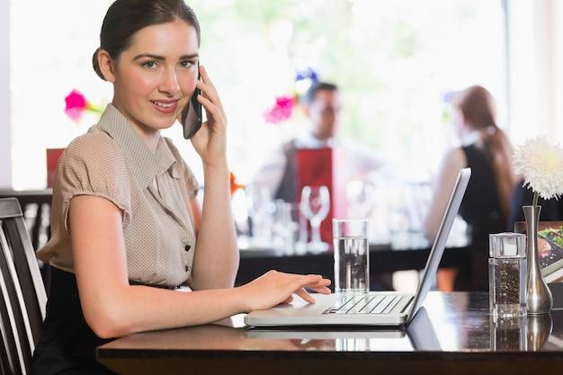 Geschäftsfrau, die am telefon unter verwendung des laptops ersucht