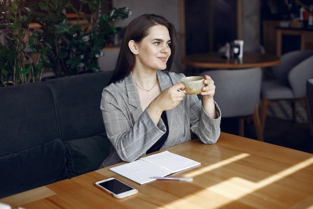 Geschäftsfrau, die am tisch in einem café und in einem arbeiten sitzt