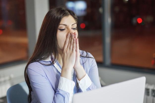 Geschäftsfrau, die am tisch mit laptop nachts im büro arbeitet. außerhalb des fensters leuchten mehrfarbige lichter