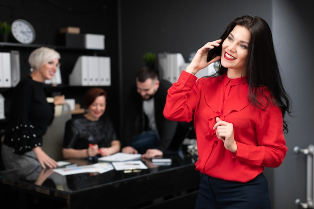 Geschäftsfrau, die an am telefon von den büroangestellten besprechen projekt spricht