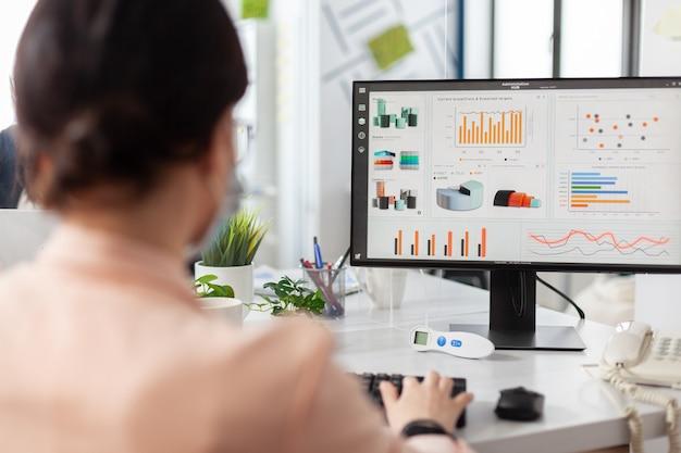 Geschäftsfrau, die an der finanzdarstellung arbeitet, die firmendiagramme analysiert