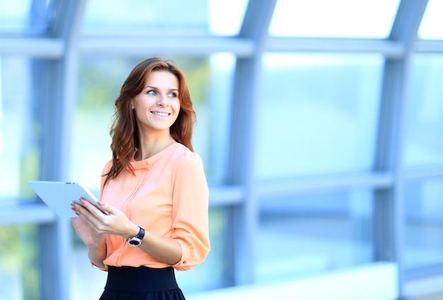 Geschäftsfrau, die an digitalem tablette im freien über gebäudehintergrund arbeitet