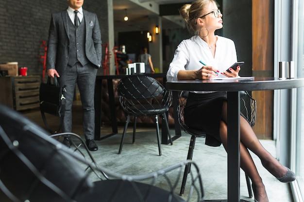 Geschäftsfrau, die an dokument im restaurant arbeitet