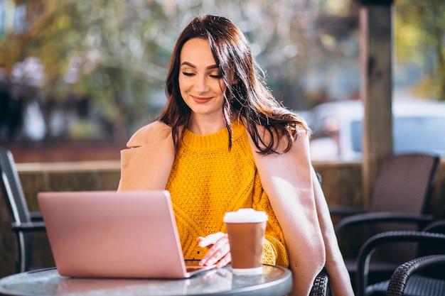 Geschäftsfrau, die an einem computer arbeitet und kaffee trinkt