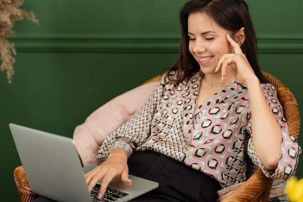 Geschäftsfrau, die an einem laptop arbeitet, der zu hause sitzt und ihr geschäft über das home-office verwaltet