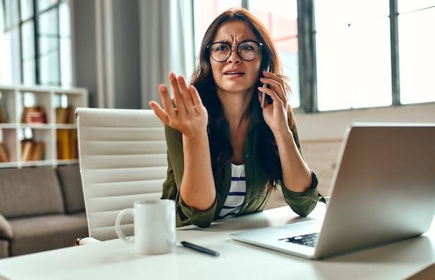 Geschäftsfrau, die an einem laptop arbeitet, während sie zu hause an einem tisch sitzt und telefoniert. freiberuflich, arbeit von zu hause aus.