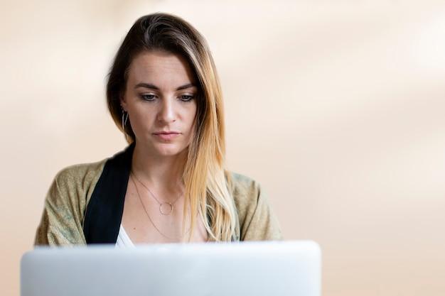 Geschäftsfrau, die an einem laptop mit designraum arbeitet