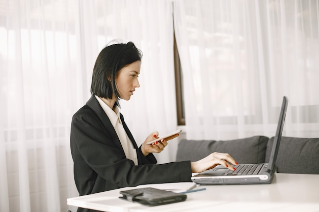 Geschäftsfrau, die an einem tisch sitzt, der am laptop arbeitet.