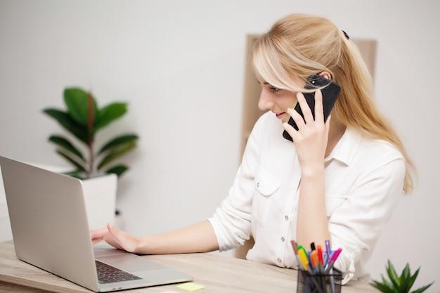 Geschäftsfrau, die an ihrem laptop im büro arbeitet.