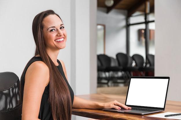 Geschäftsfrau, die an ihrem laptopmodell arbeitet