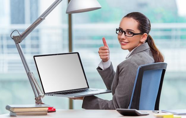 Geschäftsfrau, die an ihrem schreibtisch im geschäftskonzept sitzt