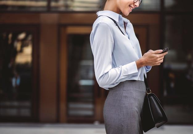 Geschäftsfrau, die an ihrem telefon simst