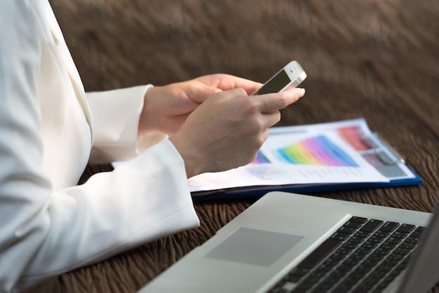 Geschäftsfrau, die an laptop arbeitet, indem sie oben auf smartphone, abschluss sucht und schreibt.